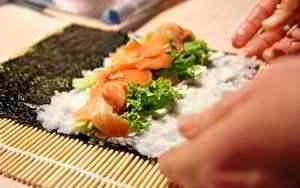 Sushi mit einer Bambusmatte rollen